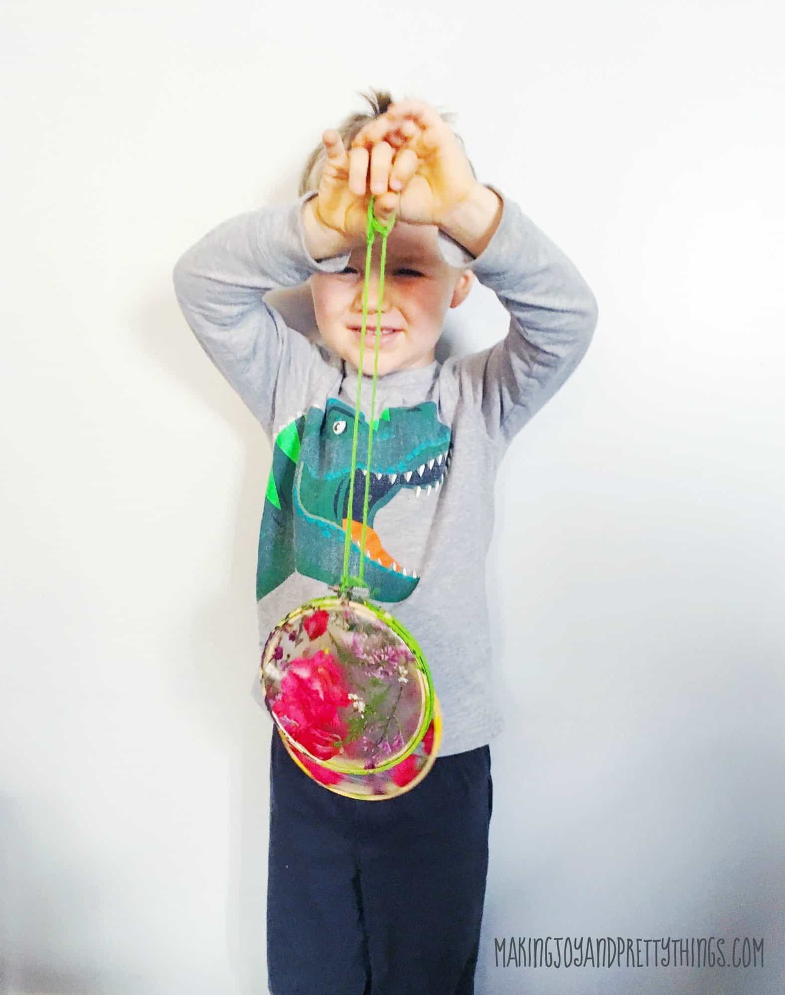 Easy DIY suncatcher craft for kids. Perfect gift for grandmothers and mothers for Mother's Day! Also great spring and summer outdoor craft for kids.
