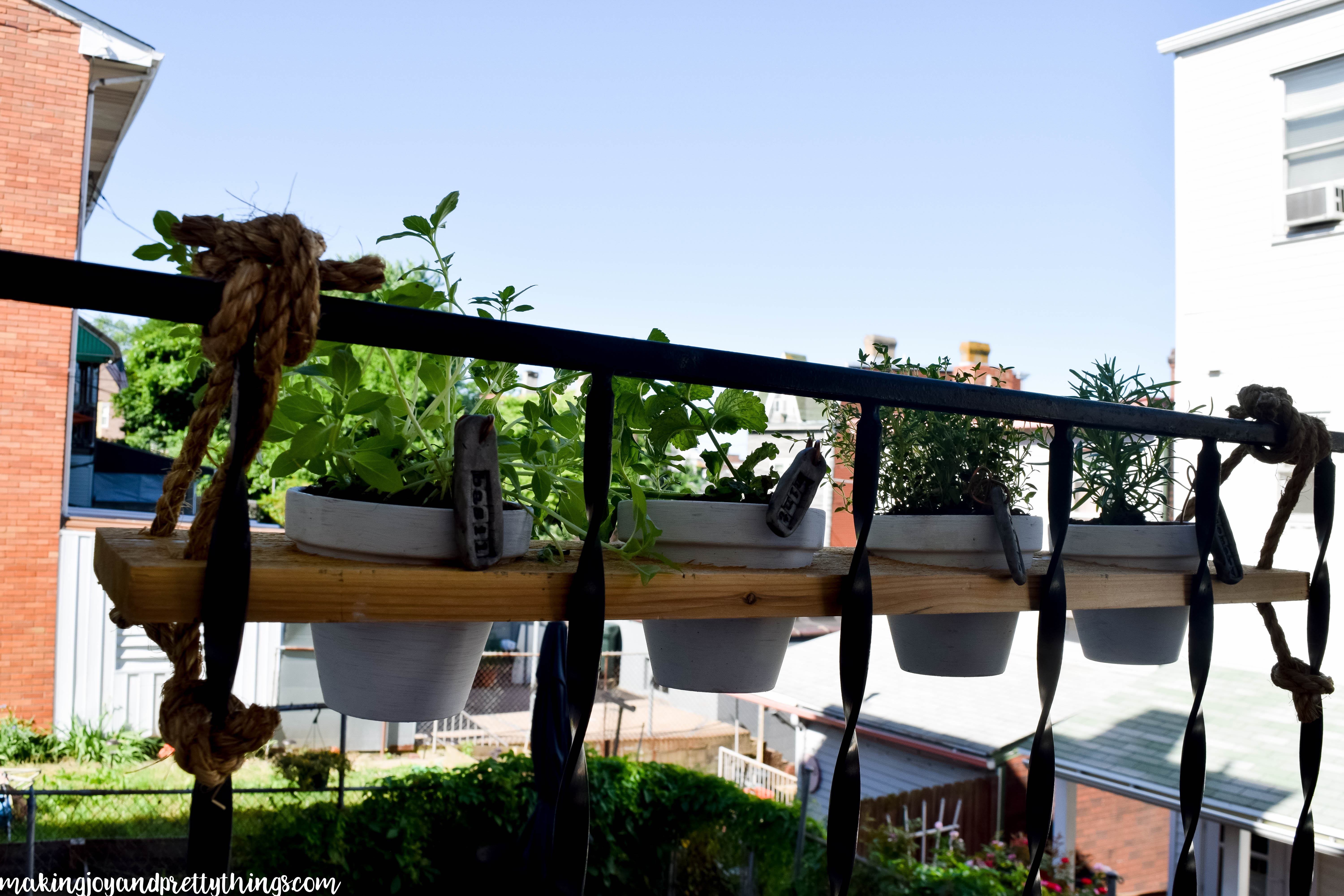 You HAVE to check out this amazing DIY hanging herb garden!! Perfect DIY herb garden for a small outdoor space. Hangs on a railing like a window box!