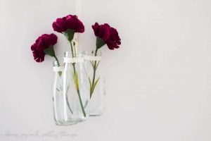 An easy farmhouse style DIY using milk jars and single stem flowers to make DIY hanging glass jars